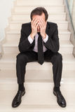 Concerned Businessman sitting with head in hands on steps Royalty Free Stock Images