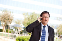 Concerned Businessman Talks on His Cell Phone Royalty Free Stock Image