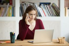 Concerned businesswoman solving company problems over phone. Stressed concerned businesswoman talking over phone, browsing internet, solving company financial Stock Photo