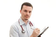 Concerned Doctor. A concerned young caucasian male doctor writes notes Royalty Free Stock Image