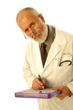 Concerned doctor. Older, experienced doctor looking concerned as he is writing up the diagnosis; isolated on white Royalty Free Stock Images