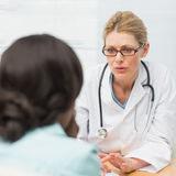 Concerned doctor talking to her patient stock photos