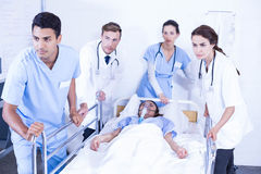 Concerned doctors standing near patient on bed. In hospital Royalty Free Stock Photos
