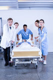 Concerned doctors standing near patient on bed. In hospital Royalty Free Stock Image