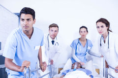 Concerned doctors standing near patient on bed. In hospital Royalty Free Stock Photo