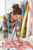 Concerned dressmaker woman looking on garment Stock Photography