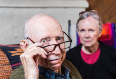Concerned Elderly Couple. Sitting in livingroom scowling Stock Images