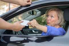 Concerned elderly driver handing over her licence. Concerned elderly women driver handing over her licence to a men reaching towards the open window during a Stock Photos