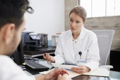 Concerned female doctor in consultation with male patient royalty free stock photography
