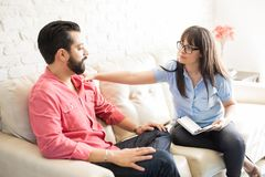 Concerned psychotherapist comforting patient. Concerned female psychotherapist comforting male patient in the office Royalty Free Stock Image