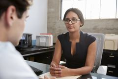Concerned female therapist counselling young male patient stock photography