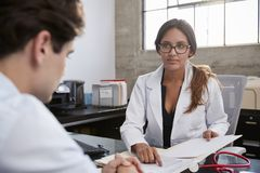 Concerned female therapist counselling young male patient royalty free stock photos