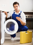 Concerned handyman fixing technical problems with washer. Professional mechanic repairing washing machine in domestic interior royalty free stock image