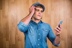 Concerned hipster looking at smartphone Royalty Free Stock Photo