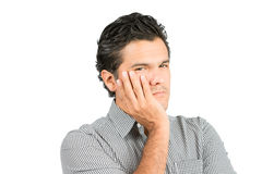 Concerned Hispanic Male Cupping Face Hand At. Portrait of concerned, worried hispanic male in casual clothes cupping face in hand looking at camera, thinking stock images