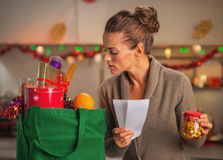 Concerned housewife with checks exploring christmas purchases Stock Images