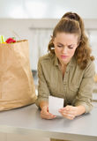 Concerned housewife examines check after shopping Stock Photography