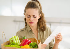 Concerned housewife examines check after shopping Stock Images
