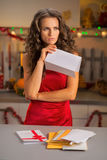 Concerned housewife holding letter in kitchen Royalty Free Stock Images
