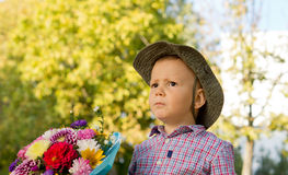 Concerned little boy with flowers Royalty Free Stock Images