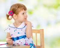 Concerned a little girl sitting at the table and Royalty Free Stock Photo