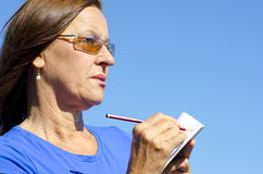 Concerned looking Woman writing a note Royalty Free Stock Images