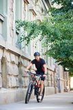 Concerned male cyclist riding in urban area. Sporty male cyclist in professional cycling sportswear and protective helmet riding bike down historical city street Stock Photo