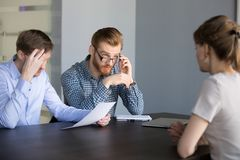 Unsure male recruiters considering female applicant candidature. Concerned male recruiters reading applicant resume, unsure about her candidature for open stock photography