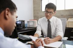 Concerned male therapist counselling older male patient stock image