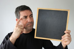 Concerned man looks at an empty blackboard Stock Image