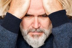 Concerned man rests head on his hands royalty free stock photo