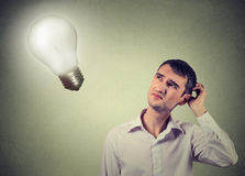 Concerned man thinks looking up at light bulb. Closeup handsome concerned man thinks looking up at bright light bulb isolated on gray wall background. Idea Royalty Free Stock Images