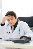 Concerned medical doctor picking up phone Royalty Free Stock Photo