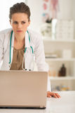 Concerned medical doctor woman with laptop. Portrait of concerned medical doctor woman with laptop in office Royalty Free Stock Photos