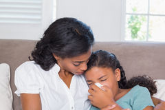 Concerned mother cuddling sick daughter Stock Photography