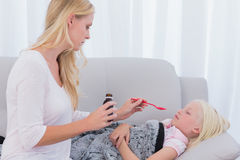 Concerned mother giving her daughter medicine. On the couch Stock Photography