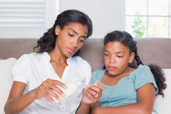 Concerned mother giving her sick daughter medicine Stock Photo