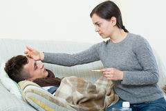 Concerned mother giving mixture to son with quinsy Royalty Free Stock Photos