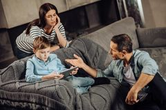 Concerned parents lecturing son on harm of binge-playing. Listen to us. Concerned young parents being near their pre-teen son seated on the couch and playing on Stock Images