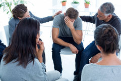 Concerned patients comforting another in rehab group. At a therapy session Stock Photo