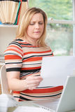 Concerned Pregnant Woman Working In Home Office Royalty Free Stock Image