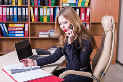 Concerned pretty lady talking on phone in office Stock Image