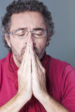 Concerned 40's man closing his eyes to think about his loss or distraught. Worried middle age man with salt and pepper hair and eye glasses with praying hands in Royalty Free Stock Photography
