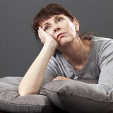 Concerned 50's woman thinking about her loss, distraught or having the blues Royalty Free Stock Photos
