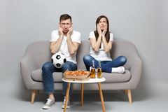 Concerned sad couple woman man football fans in white t-shirt cheer up support favorite team with soccer ball isolated. Concerned sad couple women men football stock photography