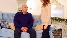 Concerned with sad thoughts, beautiful husband needs support of loving wife. married couple is sitting on blue sofa on. Serious bald man and husband sits alone stock footage