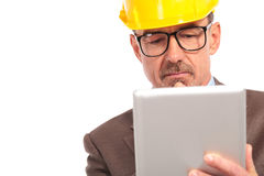 Concerned senior construction engineer reading on his tablet Royalty Free Stock Images