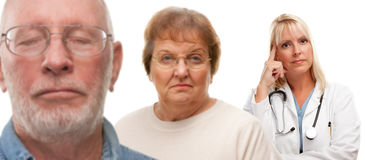 Concerned Senior Couple and Female Doctor Behind. With Selective Focus the Doctor in the Back Royalty Free Stock Photos