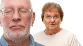 Concerned Senior Couple Isolated on White. Concerned Senior Couple with Selective Focus the Woman in the Back Stock Photos