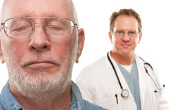 Concerned Senior Man with Doctor Behind. Concerned Senior Man with Male Doctor Behind Isolated on a White Background Stock Photo